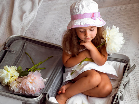 only 3 people: beautiful little girl sitting in suitcase with toys backpack on the shoulders of beautiful flowers
