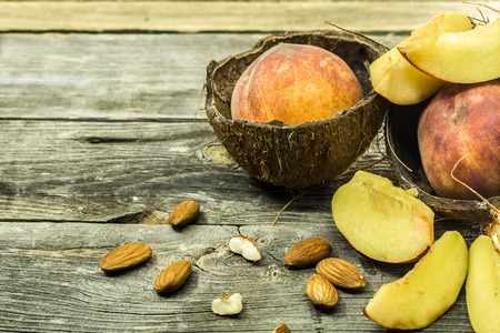 apricot kernel: Sliced and whole juicy peaches in coconut shell on wooden background, place for text, closeup