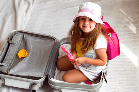 3 persons only: beautiful little girl sitting in suitcase with toys backpack on the shoulders of beautiful flowers