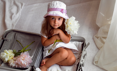 three months old: beautiful little girl sitting in suitcase with toys backpack on the shoulders of beautiful flowers