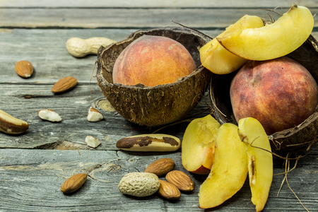apricot kernels: Sliced and whole juicy peaches in coconut shell on wooden background, place for text, closeup