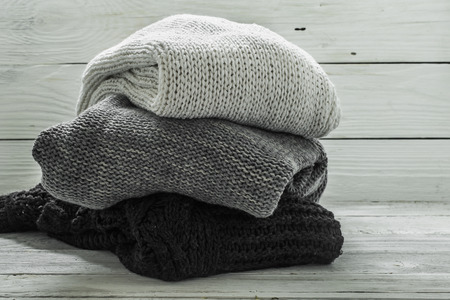 warm knitted sweater, three pieces, black,grey and white on a wooden white background, closeup Banque d'images