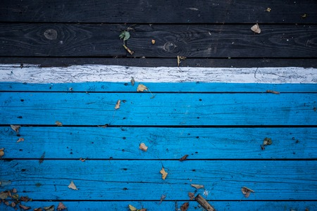Vintage wooden dark wood, half painted in blue. Front view with copy space. The horizontal Board. Background for design. wooden background. Autumn