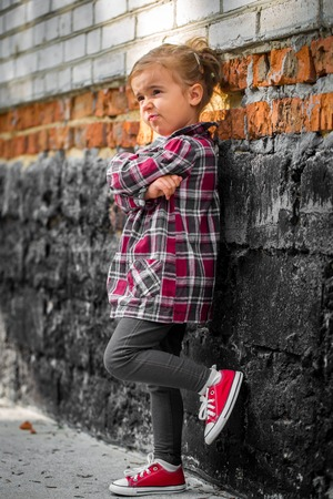 llittle beautiful girl near brick wall with red sneakers and a plaid shirt, emotion girl