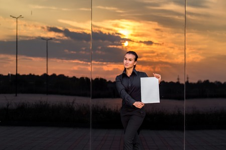 purposeful: beautiful business girl with white piece of paper on a beautiful mirror background, sunset, purposeful girl