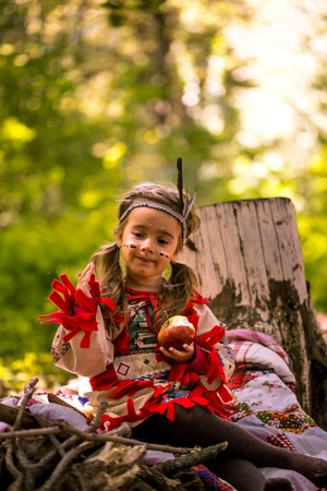 beautiful little girl playing outdoors in Indians ,eating an Apple sitting on a stump Stock Photo