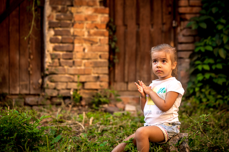 beautiful little girl playing near abandoned buildings and old doors on a summer day, the emotions of a child Stock Photo