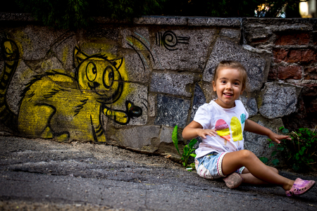 beautiful little girl playing on the pavement, drawing with a kitten on the fence of an abandoned building, the emotions of a child