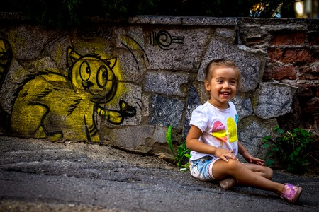 abandoned building: beautiful little girl playing on the pavement, drawing with a kitten on the fence of an abandoned building, the emotions of a child
