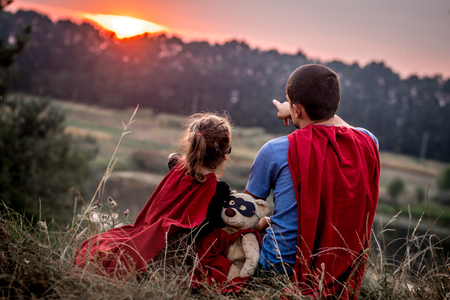 little girl with dad dressed in super heroes, happy loving family, father and daughter playing outdoors, family values