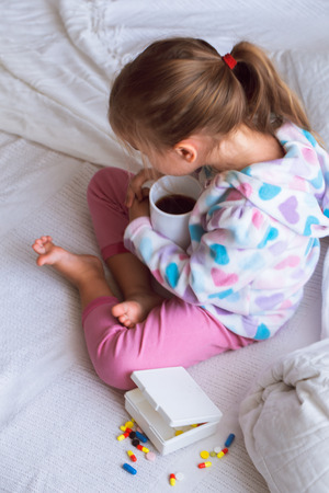 one child: diseased little girl in a white bed, dressed in warm clothes and scarf with a Cup of tea in hand