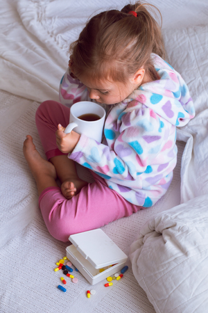 diseased little girl in a white bed, dressed in warm clothes and scarf with a Cup of tea in hand