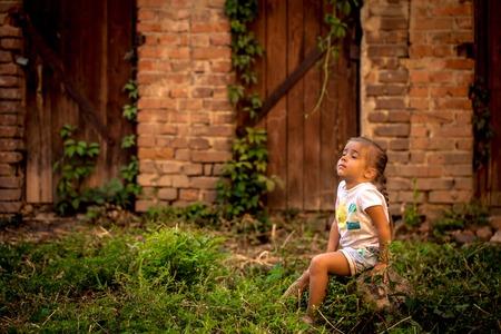puertas antiguas: hermosa niña jugando cerca de edificios abandonados y puertas viejas en un día de verano, las emociones de un niño