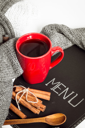 red cup: Black leaf menu with red Cup with cinnamon and Cutlery
