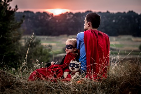 super dad: little girl with dad dressed in super heroes, happy loving family, father and daughter playing outdoors, family values