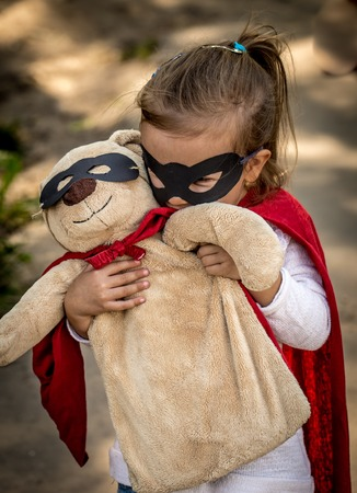 beautiful little girl in the image of a super hero, playing with the soft toy Department of a bear into a super hero Stock Photo