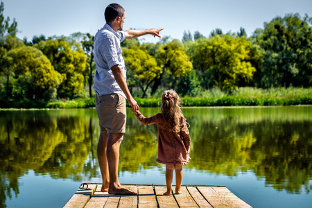 Dad with daughter on shoulders stand on the pier near the lake Stock Photo