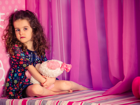 soft toys: little girl playing with soft toys near the window in a baby pink room Stock Photo