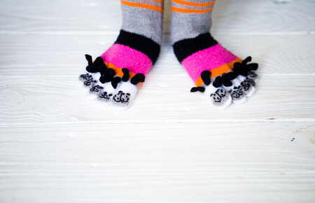 Baby feet in warm, long multicolored socks with toes white background