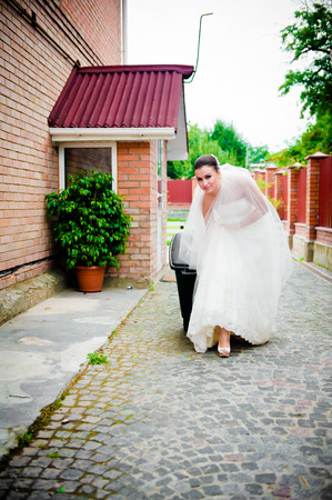 garbage collection: beautiful girl in a wedding dress and a veil garbage collection before the wedding
