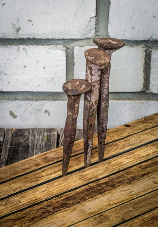 very old large nails on a beautiful wooden background, rusty nails, there is a place for text Stock Photo