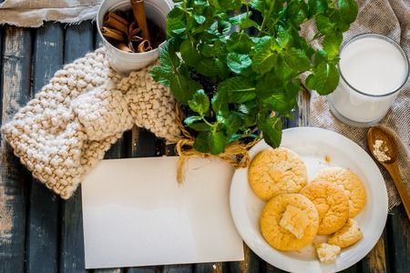 Still life on a wooden table with a plate of cookies and a glass of milk.A pot of mint and white envelope.Place for text Stock Photo