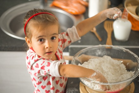 beautiful little girl Baker on kitchen with ingredients for baking Фото со стока