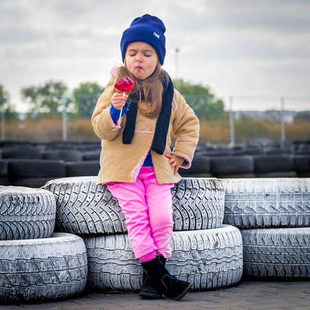 beautiful stylish little girl with glasses on the background of the racing tracks, emotions, girls, large inflated lips in the form of candy 스톡 콘텐츠