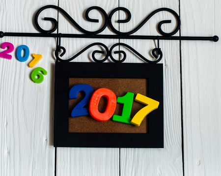 expiring: Expiring 2016.New year 2017, the figures in the picture frame on white wooden background.