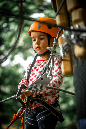 adventuring: sports happy kid climbs through the ropes, the beautiful girl in the outfit climbing fun in the forest on ropes and different obstacles Stock Photo