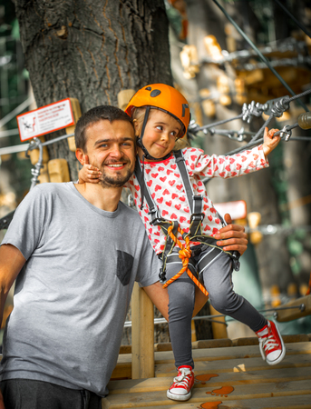 adventuring: sports happy child with father climbs over the ropes, beautiful girl in the outfit climbing fun in the forest on ropes and different obstacles, family friendly Stock Photo