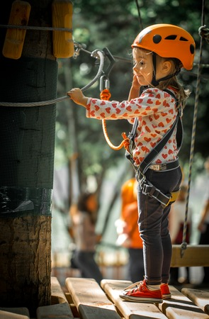sports happy kid climbs through the ropes, the beautiful girl in the outfit climbing fun in the forest on ropes and different obstacles Stock Photo