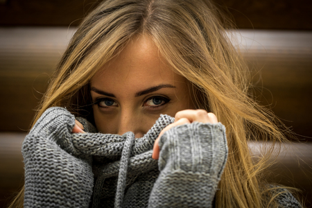 Beautiful girl in a sweater with long hair and red lips is on the background of wooden logs Stock Photo