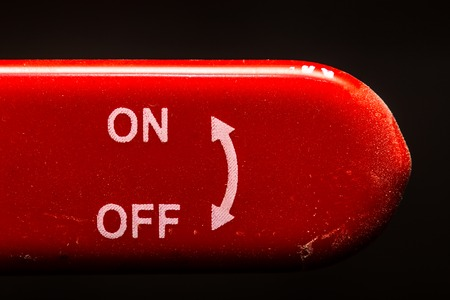or electrocution: the red lever on off switch on dark background, closeup