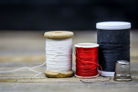Sewing thread black , white and red with a thimble beautifully folded on a wooden background