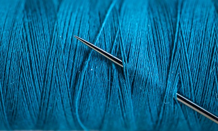 Sewing thread beautiful colors with needle closeup