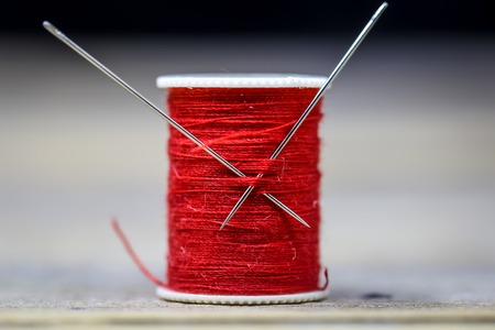Sewing thread red with two needles closeup on wooden background