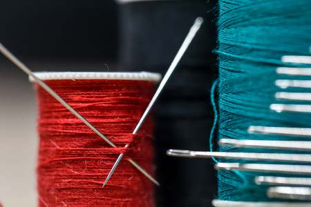 Sewing threads of different colors with lots of needles closeup on wooden background