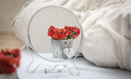 reflection of flowers in a pot with a heart in a round mirror standing on a white bed