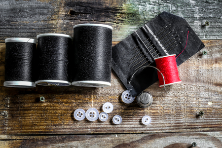 individually: set of sewing threads and accessories on wooden background contrast individually. Stock Photo
