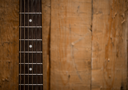 fingerboard: fingerboard from the acoustic guitar on wooden background, closeup