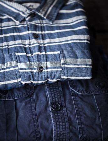 Beautiful stylish mens clothing, shirts folded in a pile on wooden background Stock Photo