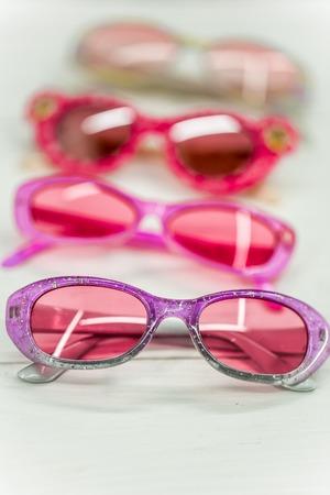 elementos de protección personal: hermosas niños gafas de sol de color rosa sobre fondo blanco