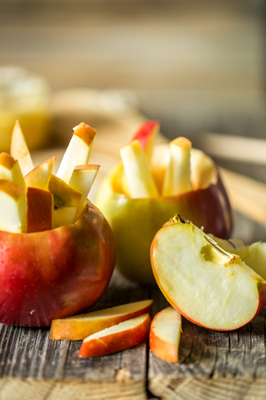 Still life with apples on wooden background . Apples cut into strips.
