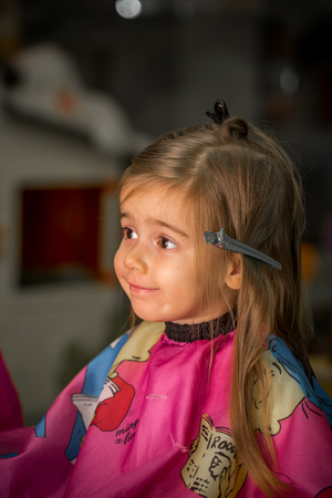 Beautiful little girl with long hair, obostryaet hair at the hairdresser