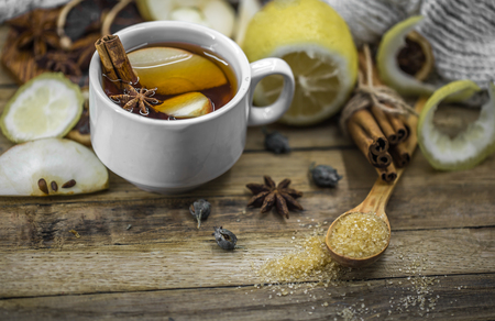 a Cup of hot tea with lemon, a cinnamon stick and a spoonful of brown sugar on wooden background, holiday concept and warm mood Stock Photo