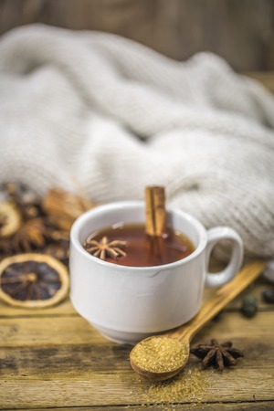 a Cup of hot tea with a cinnamon stick and a spoonful of brown sugar on wooden background, holiday concept and warm mood