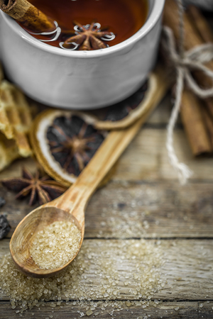 punch spice: a Cup of hot tea with a cinnamon stick and a spoonful of brown sugar on wooden background, holiday concept and warm mood