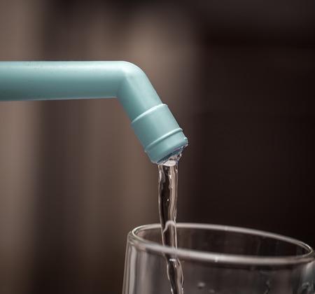 utensilios de cocina: Water filter is poured into a transparent glass closeup