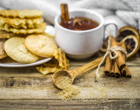 delicious cookies and a Cup of hot tea with a cinnamon stick and a spoonful of brown sugar on wooden background, holiday concept and warm mood